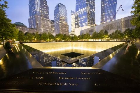 The rim of the 9/11 Memorial pool is illuminated from inside. A man leans over the side of the names parapet. Skyscrapers surround the scene at dusk.