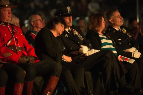 Sonia and Joe Agron embrace while seated at an event. Joe is in a formal NYPD uniform.