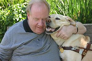 Michael Hingson embraces his guide dog Roselle in the shade of trees.