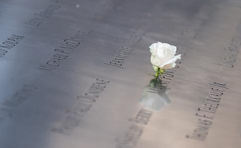 A single, white rose is placed at a name etched on a bronze parapet of the Memorial.