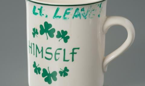 "A mug belonging to FDNY Lieutenant Joseph Leavey is displayed on a gray surface at the museum. The white mug is adorned with green shamrocks. The word ""himself"" is printed in green on the mug. Leavey's name has been written in green marker on the lip of the cup."
