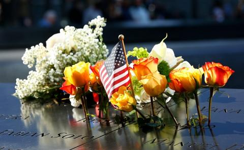 White, orange, and yellow flowers and an American flag are left as tributes are left on the Memorial plaza during the 18th anniversary ceremony in New York on Wednesday, September 11, 2019.