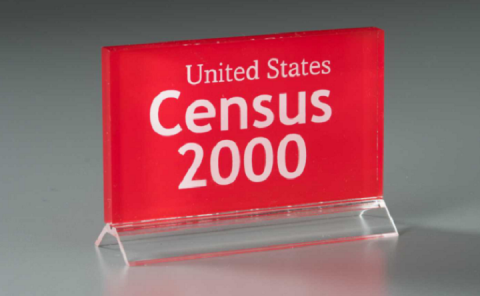 "In front of a gray background, a red and clear lucite plaque reads ""United States Census 2000."""