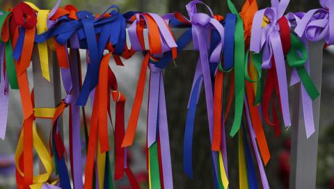 Dozens of rainbow-colored ribbons are tied around a metal post.