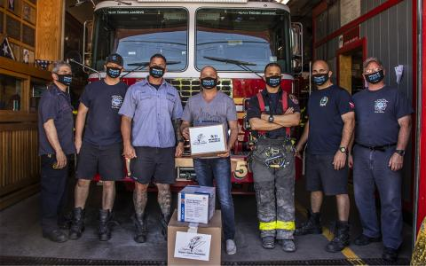 Six firefighter stand in front of a firetruck at a firehouse on Staten Island.   In the center of the firemen, an employee of the 9/11 Memorial Museum stands holding a box of masks that were delivered to the fire house.