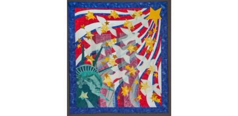 Handmade textile quilt depicts the Twin Towers at center, ghostlike in their transparency. The crowned head of the Statue of Liberty is represented in the lower left corner of the quilt, and from it white doves and yellow stars emanate. These images are set against waves of red, white, and blue.