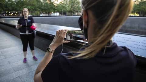 A woman uses a smartphone to film another woman addressing the camera at the 9/11 Memorial.