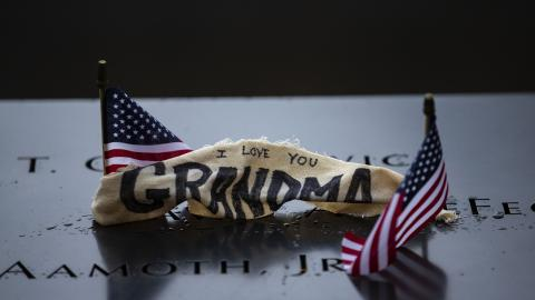 "A cloth with a hand-written note has been placed at a victim's name on a bronze parapet at the Memorial. The cloth reads ""I love you grandma"" and sits between two, small American flags."