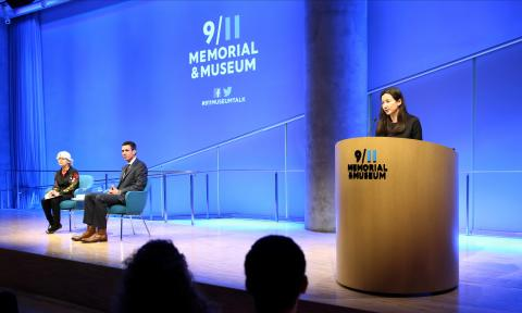 "A man and a woman sit on stage during a public program in the Museum auditorium. A second woman stands at a wooden podium, speaking to the audience. Blue light fills the wall behind the stage and a projection on the wall reads ""9/11 Memorial & Museum."""