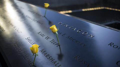 Three yellow roses stand at the names of victims etched on a sunlit Memorial. The names are near the inscription indicating Pentagon victims. The water of a reflecting pool can be seen further afield.