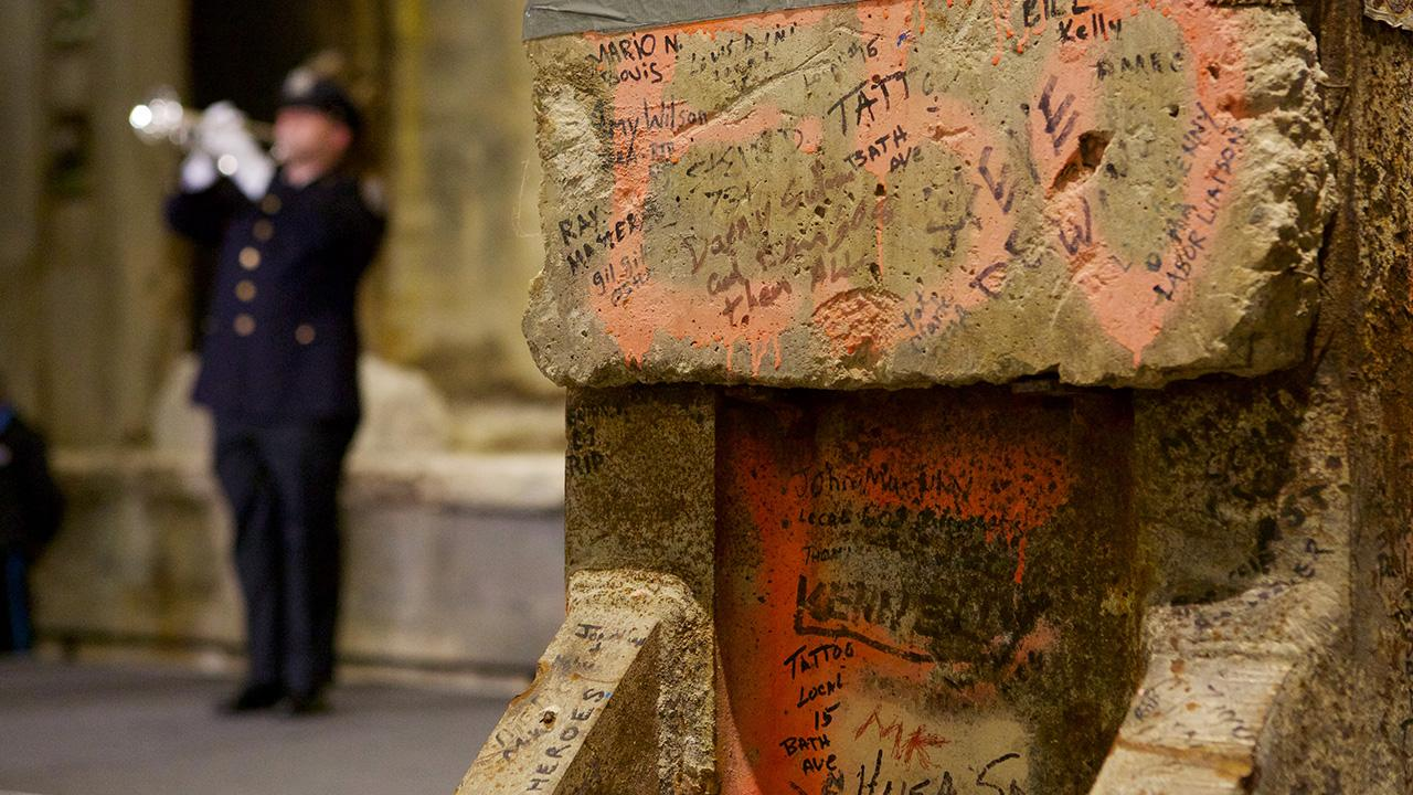 "An NYPD officer in formal clothing plays ""Taps"" on a trumpet near the Last Column during a ceremony in Foundation Hall. The officer is to the left and out of focus. In the foreground, details of the Last Column, including handwritten messages and orange marking paint, are visible."