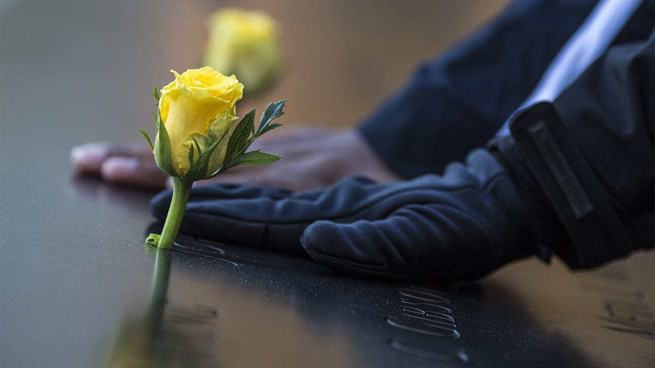 A person's gloved hand touches a name adorned with a yellow rose on a bronze parapet at the Memorial. The hand of a second person is between the first hand and a second yellow rose.