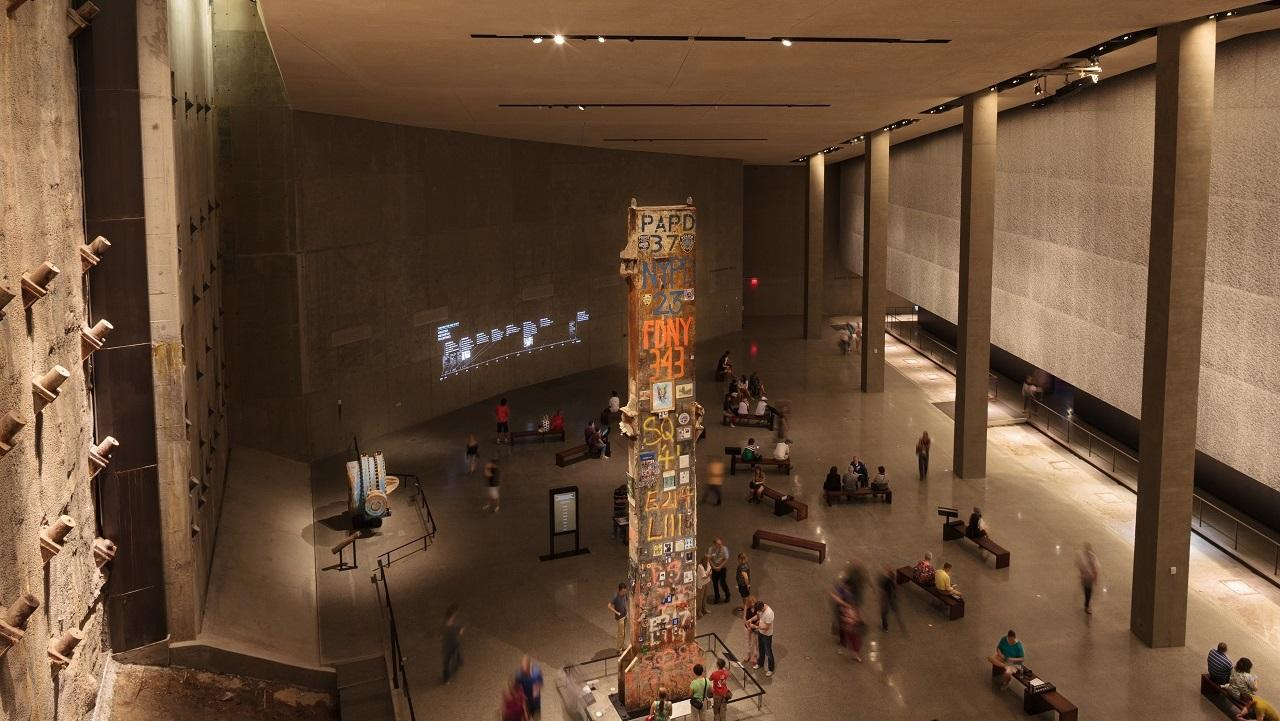 A view from above shows visitors gathering around the Last Column, a thirty-six-foot-tall steel beam that was the last to be removed from Ground Zero. In the distance, visitors observe information about 9/11 projected on a wall.