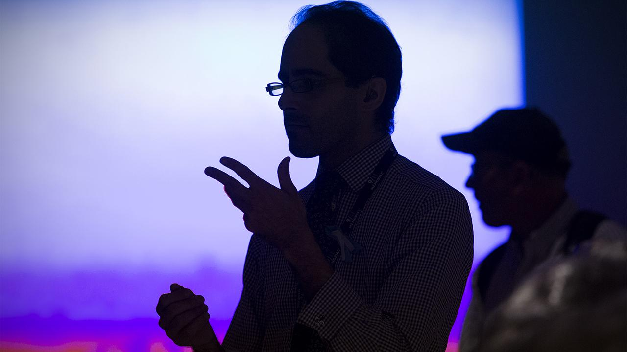 A man speaking in sign language is silhouetted against a bright screen at the Museum.