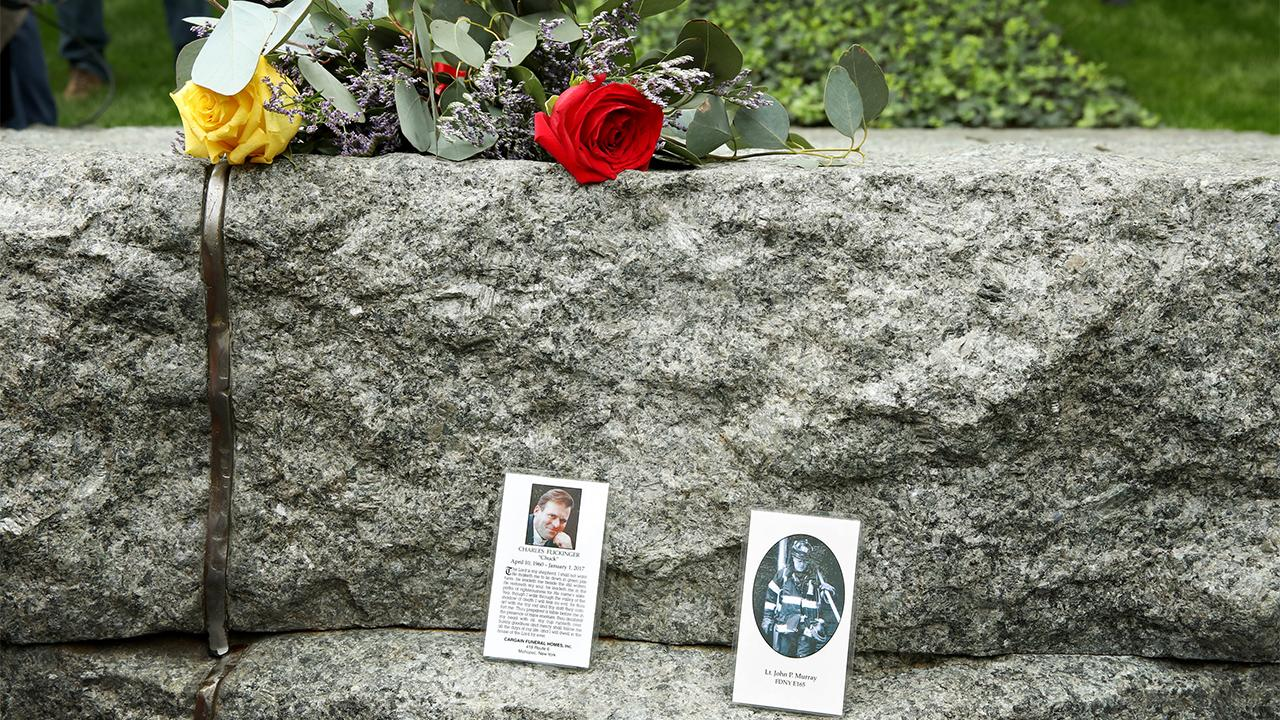 Two laminated tribute cards have been placed upright on a stone monolith at the Memorial Glade. A photo of a man is on the card to the left and a photo of a firefighter is on the card to the right. Above the cards is a bouquet of flowers, including a yellow rose and a red rose.