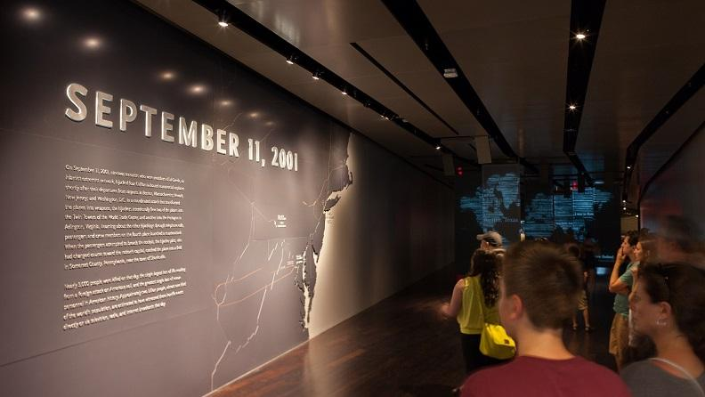 Visitors walk down a dimly lit hall. Beside them is a large map of the Eastern United States that shows the routes the hijacked planes took.