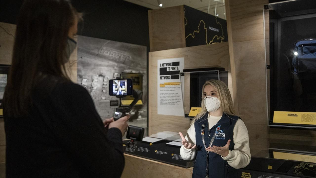 "A tour guide wearing a mask stands in the ""Revealed"" exhibition space to give a virtual tour. Another Museum staff member films the tour with her back to the camera."