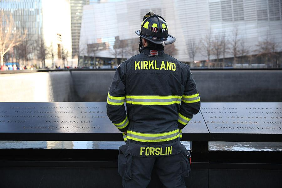 "A firefighter pauses in reflection on 9/11 Memorial plaza as he looks out over a reflecting pool. The firefighter is wearing bunker gear that says ""Kirkland"" on the back."