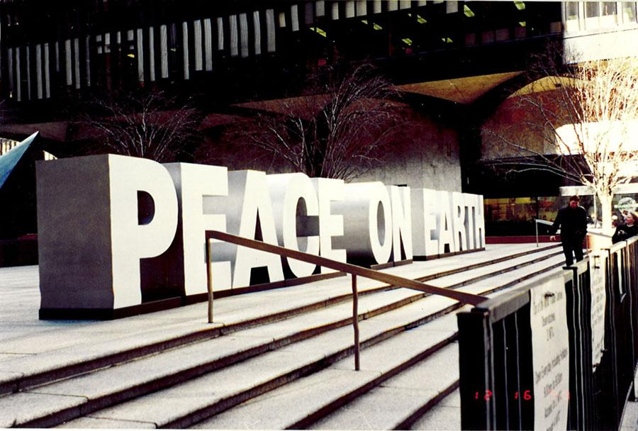 "A large ""Peace on Earth"" sign is displayed on the steps of the World Trade Center in 1999."