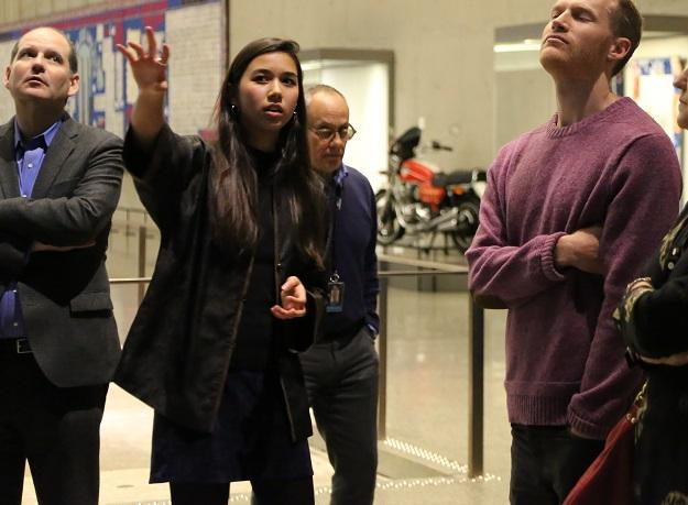 Annalee Tai, a 9/11 Museum ambassador, leads a tour at the Museum. Several visitors stand beside her as she points towards something out of view.