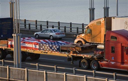 A-steel-beam-salvaged-from-the-World-Trade-Center-is-transported-across-the-George-Washington-Bridge-in-New-York-on-its-way-to-Coatesville-Penn.-Wednesday-April-14-2010.-A-mile-long-convoy-of-28-tractor-traile.jpg
