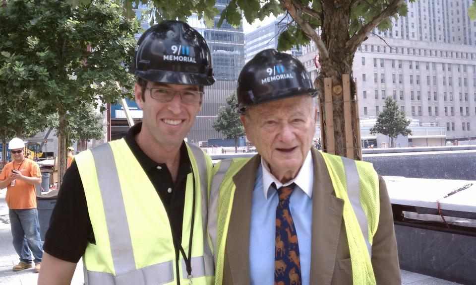 9/11 Memorial architect Michael Arab and former New York City Mayor Ed Koch smile for a photo on Memorial plaza. They are both wearing 9/11 Memorial hardhats.