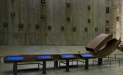 A large rusty beam from the Twin Towers is displayed beside four signing screens in Foundation Hall. The concrete slurry wall is visible in the background.