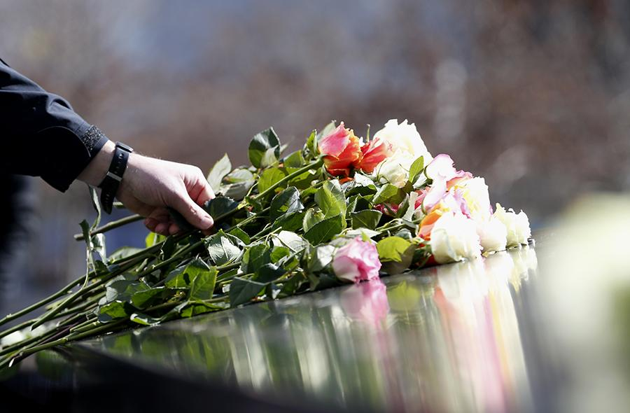 A person places a bundle of multicolored roses at a name on a bronze parapet at the Memorial during a ceremony remembering the victims of the 1993 World Trade Center bombing.