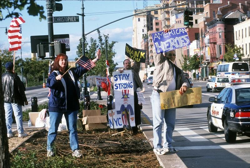 "Several people stand in the median of the West Side Highway holding signs in support of rescue and recovery workers in the weeks after September 11. The signs they're holding include messages like ""Stay Strony NYC"" and ""We Love Our Heroes."""