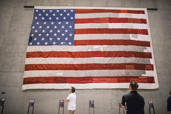 The large national 9/11 flag is displayed on a concrete wall in the south corridor of the 9/11 Memorial Museum. Two visitors are looking up at the flag.