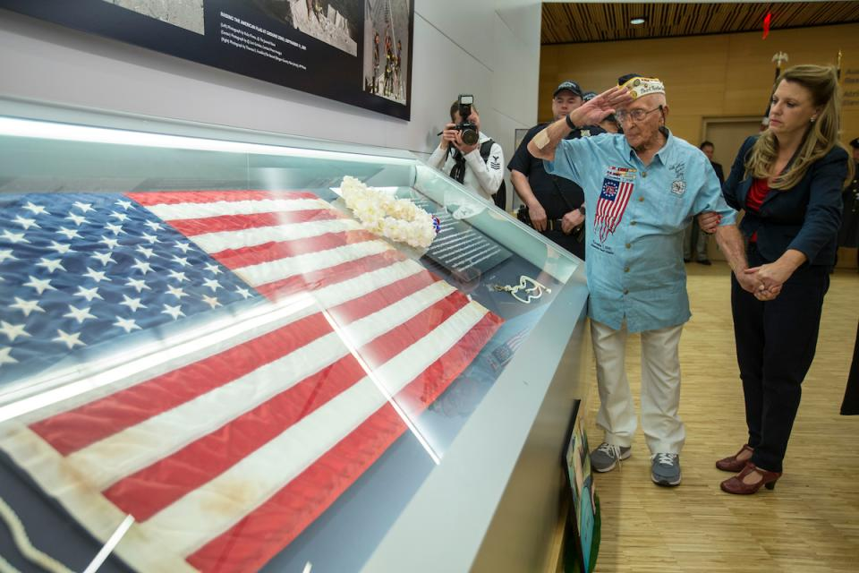 John Seelie, a U.S. Army veteran and Pearl Harbor survivor, salutes an American flag that flew at Ground Zero as he stands beside it at the 9/11 Memorial Museum.