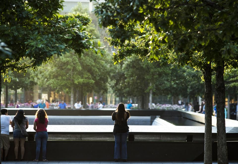 A woman stands alone as she looks out over the North Pool at the 9/11 Memorial on a summer day. Several other visitors are standing off to her left looking out at the pool. And more visitors can be seen across the pool in the distance.