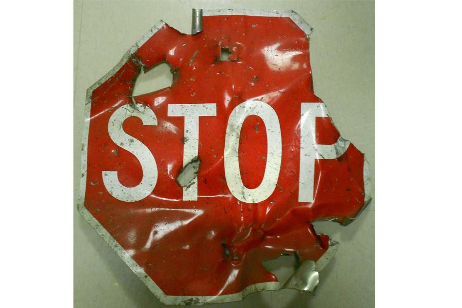 A heavily damaged red stop sign destroyed in the 1993 bombing of the World Trade Center is displayed on a white surface at the Museum.