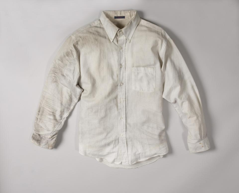 A smoke-stained white dress shirt worn by Walter Travers on February 26, 1993 is displayed on a white surface at the Museum.