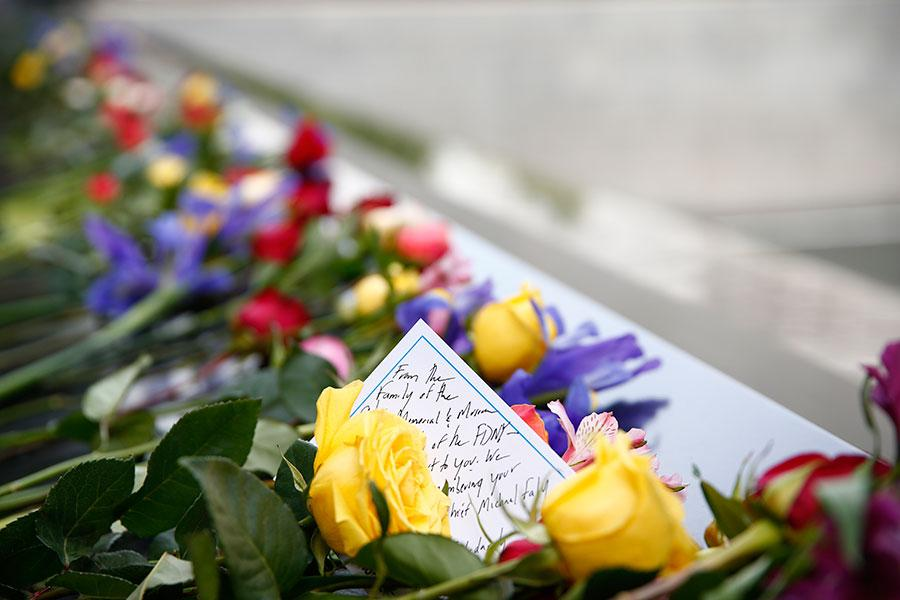 A message sits amid dozens of red, yellow, and purple flowers left on a bronze parapet in tribute to FDNY firefighter Michael Fahy.
