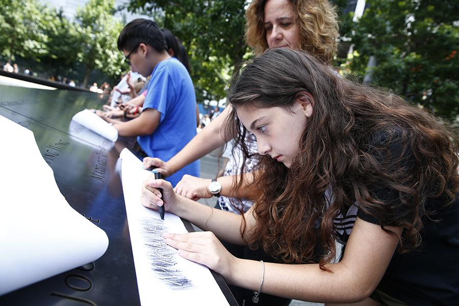 A girl stands next to a woman as she makes a charcoal rubbing at a name etched on a bronze parapet at the Memorial. Other young visitors do the same behind her.