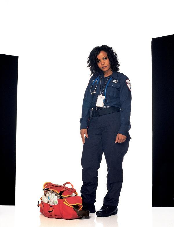 "Juana Lomi wears her uniform and stands next to her bag as she poses for a photo for Joe McNally's ""Faces of Ground Zero."""