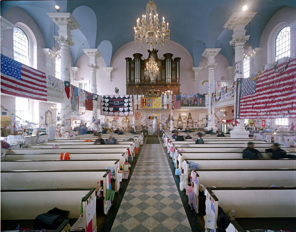 A photo from inside St. Paul's Chapel in the days after 9/11 shows American flags, tributes, and other items hanging all over the interior of the church. Several people are sitting in the pews.