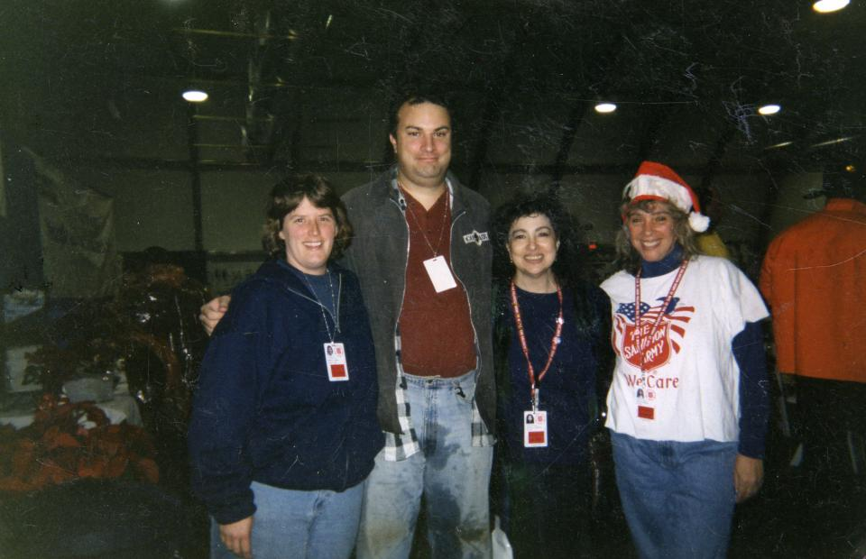 Four Salvation Army volunteers—three women and a man—pose for a photo together at the Salvation Army tent near Ground Zero in December 2001.