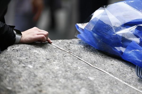 A person places their hand on a granite monolith at the 9/11 Memorial Glade. A bouquet wrapped in a blue flower sleeve sits to the right.
