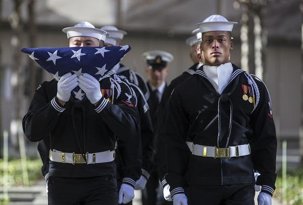 Members of the U.S. Navy stand in formation during a flag-folding ceremony on 9/11 Memorial plaza. One of them is holding up a U.S. flag in front of him.
