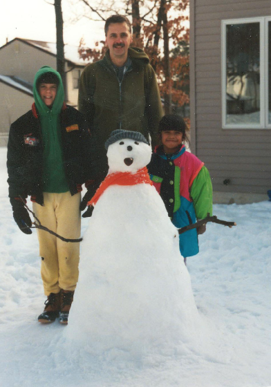Michael Diehl stands in the snow next to a snowman with his two children, a boy and a girl.