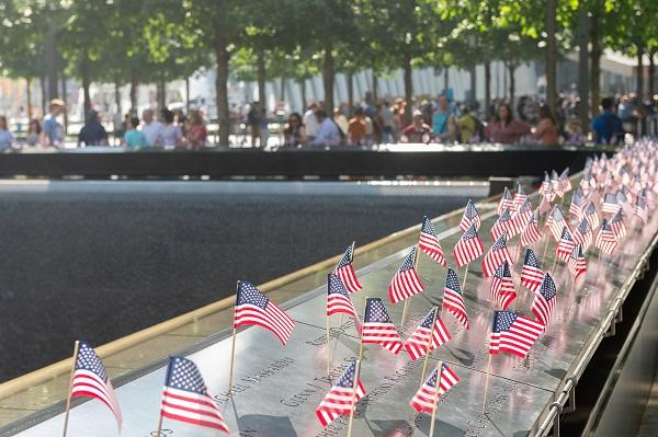 Dozens of small American flags have been placed at the names of victims at the 9/11 Memorial on a sunny day. Visitors tour Memorial plaza in the background.