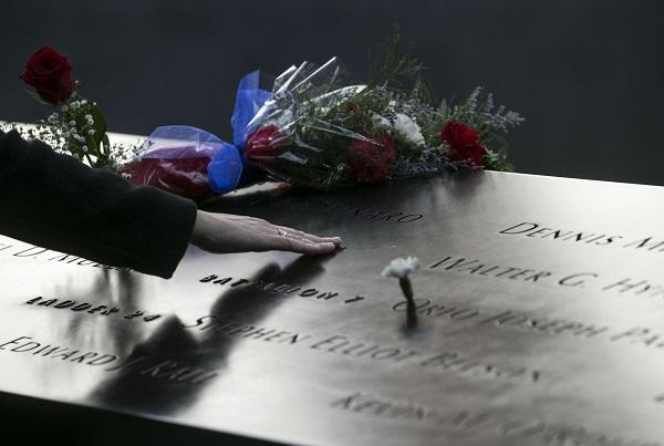 A person places his or her hand at a name on the 9/11 Memorial during the 16th anniversary commemoration ceremony at Memorial plaza.
