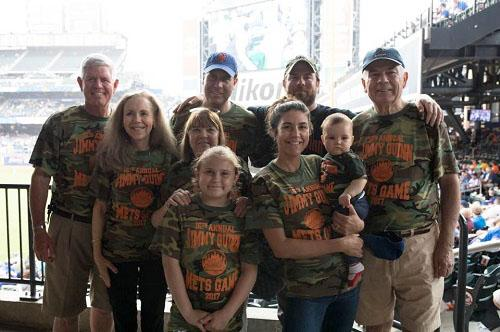 "Joe Quinn and friends and family of Jimmy Quinn attend the 16th annual Jimmy Quinn Mets game. They are wearing camouflage shirts that read, ""16th annual Jimmy Quinn Mets Game 2017."""
