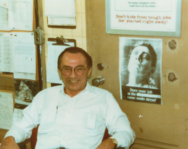This historical photo shows Robert Kirkpatrick in a white collared shirt in his office at the World Trade Center. Papers and images are tacked onto the wall behind him.