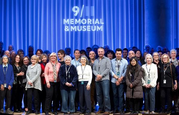 Dozens of volunteers, primarily older adults, are seen onstage at the Museum auditorium during the National Volunteer Week ceremony and reception. A blue curtain behind them has the 9/11 Memorial & Museum logo projected on it.