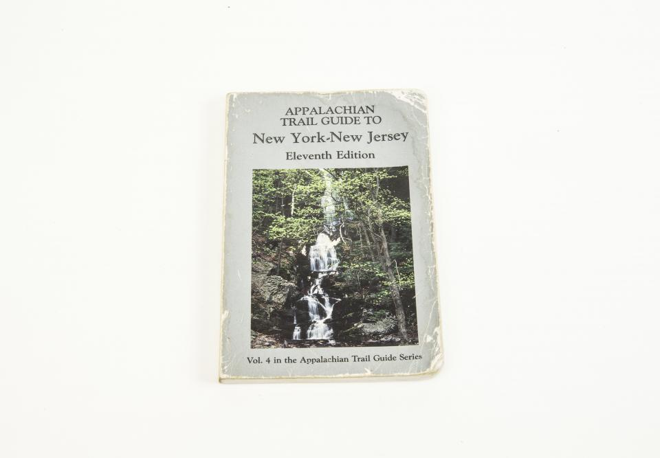 An Appalachian trail guidebook belonging to Bruce Van Hine is displayed on a white surface. The book includes a cover image of a waterfall.