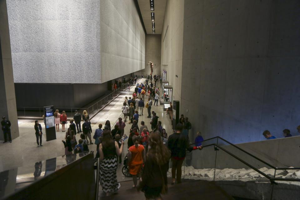 Dozens of visitors are seen in the 9/11 Memorial Museum. In the foreground, visitors pass by the Survivors' Staircase.