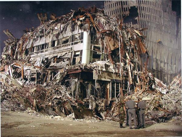 Several men in military and law enforcement garbs stand beside the smouldering remains of the Marriott World Trade Center hotel on a night shortly after the attacks. The hotel is covered in twisted debris from the Twin Towers.